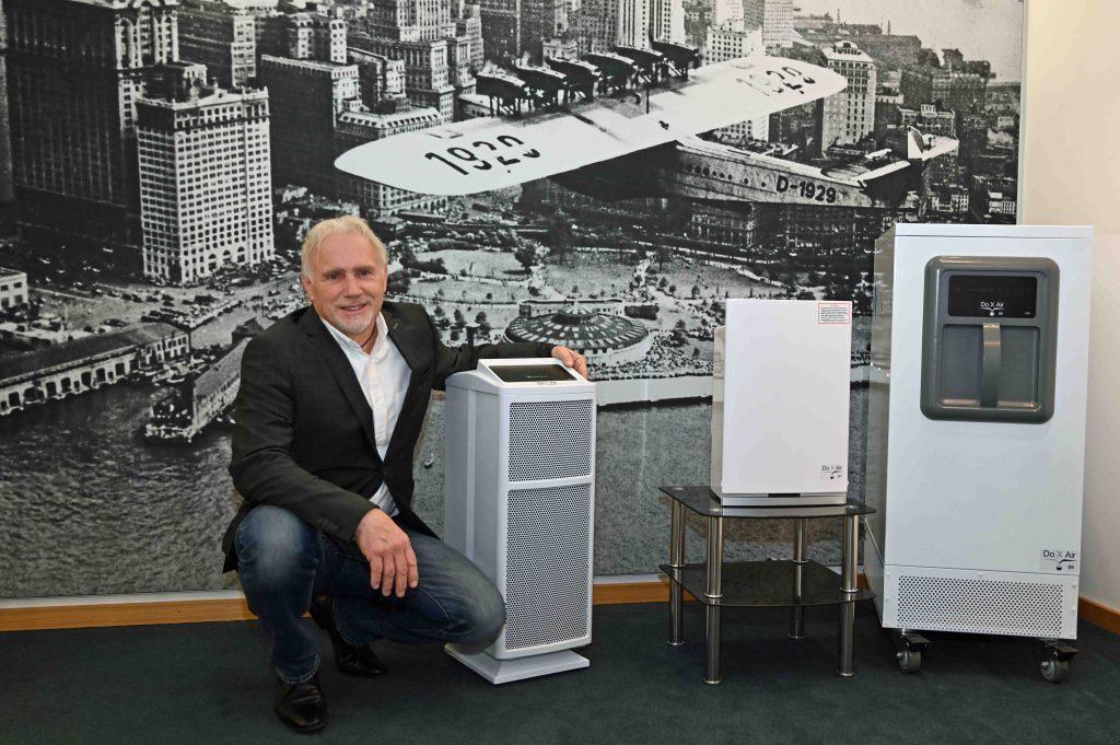 Textfeld: Irén Dorner mit den Luftreinigungsgeräten Do-X-Air 77,  Do-X-Air 07 und Do-X-Air 09. Im Hintergrund: Die legendäre Dornier Do X vor der Skyline von Manhattan